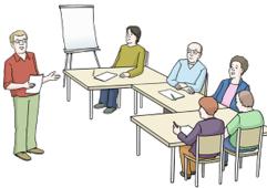 Das Bild zeigt viele Tische. An den Tischen sitzen Menschen. Es gibt auch eine Tafel. Und einen Lehrer.