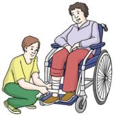 Das Bild zeigt einen Mann im Rollstuhl. Ein anderer Mann verbindet seinen Fuß.