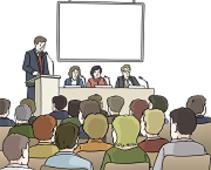 Das Bild zeigt Menschen vor einer Bühne mit Rednern